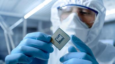 En person i skyddsdräkt inspekterar ett mikrochip.