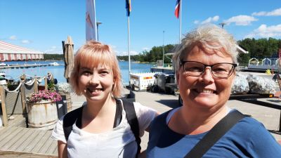 Pernilla Ekholm till vänster i vit t-skjorta, Marika Ekholm till höger i blå skjorta står i Nagu gästhamn.