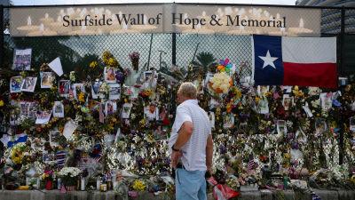 Mies katsoo muistopaikan kukkia ja viestejä.