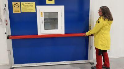 En dam i gul jacka öppnar den blå dörren till ett syrefattigt lager för äpplen.