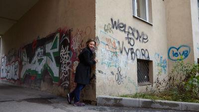 Anna Kortelainen Viipurissa syksyllä 2016. Rapistuneen seinän graffitissa lukee tekstit Welcome to Vyborg sekä Love.