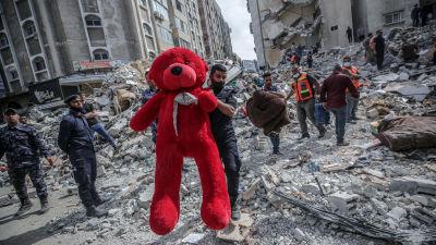 Palestinska räddningsarbetare bär bort en enorm teddybjörn ur ruinerna efter den förödande flygattacken som raserade tre bostadshus i Gaza City tidigt på söndag morgon.