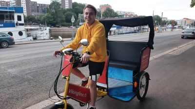 En ung man kör en gul cykeltaxi, riksha, längs en åstrand.