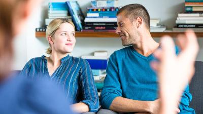 Man och kvinna sitter i soffa och ser leende på varandra