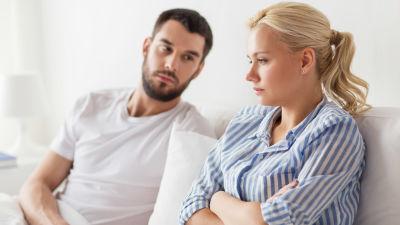 Mörkhårig man och blond kvinna sitter i soffa och ser sorgsna ut