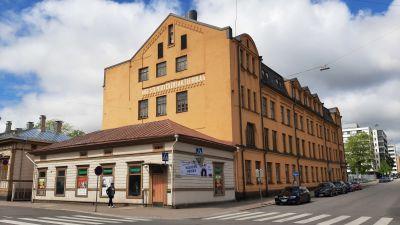 Åbo stentryckeri, en stor gul stenbyggnad i ett gathörn, med en liten ljus träbyggnad från 1821 framför sig.
