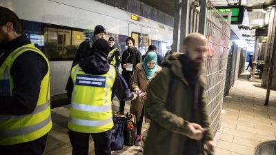 Gränskontrollanter i reflexväst kollar ID på tågpassagerare i Malmö.