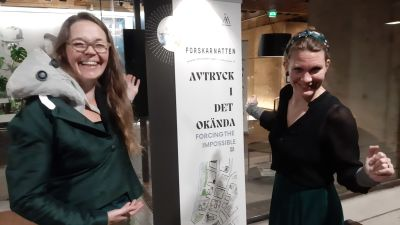 Laura Hellsten och Minna Aalto sätter upp en vit banderoll för Forskarnatten - Avtryck i det okända.