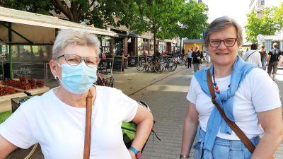 Britta Sunde och Maria Nyman, två damer med glasögon och vita t-skjortor stor en somrig sommardag på en gågata.