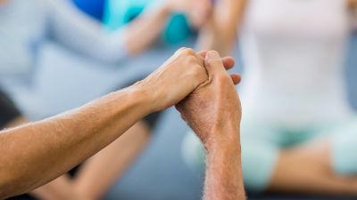 händer som håller i varandar. Det är händer på äldre mänskor. Kan tolkas som dans eller gruppgymnastik eller yoga.
