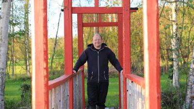 Man i mörk jacka står på röd bro.