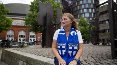 Kvinna i finska blåvita supporterfärger.