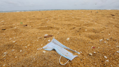 I förgrunden ligger ett munskydd i sanden, i bakgrunden skymtar havet.