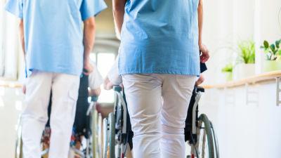 Två närvårdare som går med varsin rullstol framför sig.