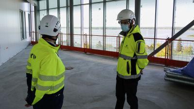 Två män i byggarbetskläder står upp på en terass högt upp. Vasa stadsfjärd syns i bakgrunden.