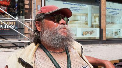 Markku Hynönen, en man med ett stort gråsvart skägg, solglasögon och en röd skärmmössa, sitter framför en byggnadsställning.