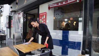 Kvinna torkar bord på en restaurang prydd med danska och finska flaggor.