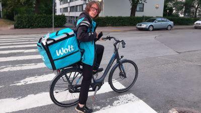 en man med glasögon cyklar med en matleverans i en klarblå låda, där det står Wolt.