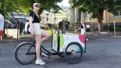 En dam med solglasögon, keps och shorts sitter på en flakcykel med färggranna bollar på lådan.