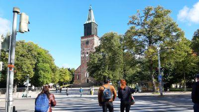 Tre unga går över ett övergångsställe vid Åbo Domkyrka.