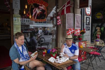 Två män i finska spelskjortor och fotbollshalsdukar sitter på en uteservering prydd med danska flaggor.