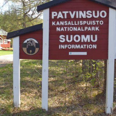 Patvinsuon kansallispuiston opastuskeskus ja opastekyltti.