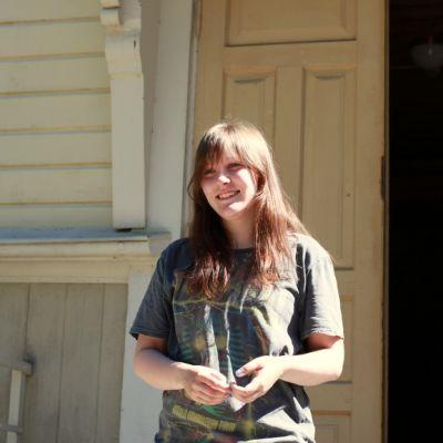 Utran kirkolla kesätyötään tekevä Anni Rask hymyilee Utran kirkon pihalla.