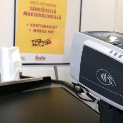 Kaupan seinällä on ilmoitus, että kaupassa voi maksaa vain kortilla tai puhelimella.