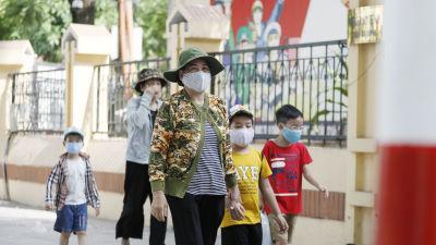 Kvinnor och barn på promenad i Hanoi på söndagen - alla utrustade med munskydd.