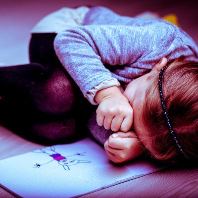 Ihopkurat barn invid sin teckning.