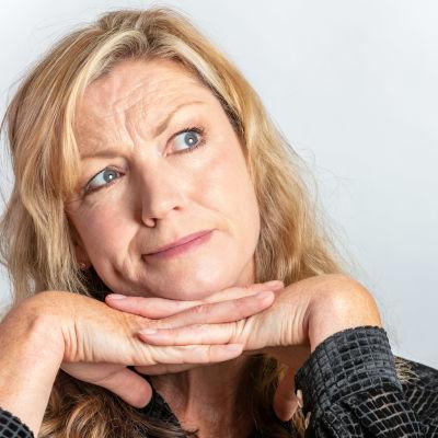 Blond kvinna gör fundersam grimas