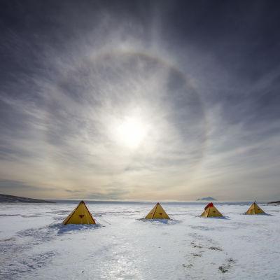 En låg sol över tält på isen i Antarktis.