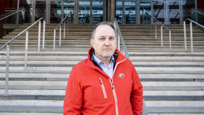 Medeleålders man i röd jacka med Vasa sports logo står vid en bred trappa utomhus.