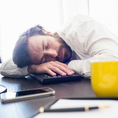 mies nukkuu työpöydällä olevan näppäimistön päällä