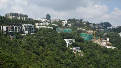Bild på en kulle med hus och en gul lyftkran.