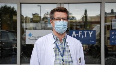 Medelålders man i munskydd och läkarrock. I bakgrunden en sjukhusingång.