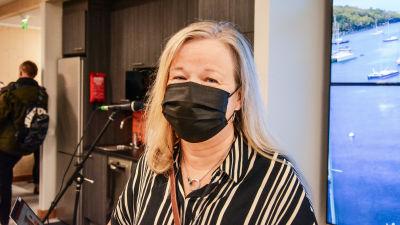 Kvinna i munskydd står i aula.
