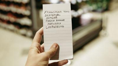 """En hand håller i en uppköpslista i en mataffär. Listan räknar upp """"fransyska 400 gram, skrädmjöl, semlor, finska pinnar, korvkaka, laxpudding""""."""
