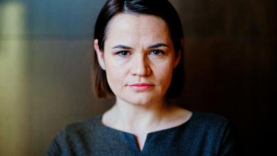Mörkhårig kvinna tittar mot kameran. Svetlana Tichanovskaja besöker Finland för att träffa landets utrikespolitiska ledning.