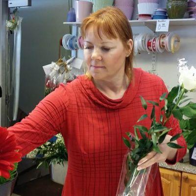 Kuvassa kukkakauppias liikkeessään.