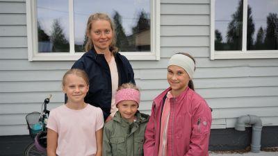 Kvinna med tre barn står framför en vit byggnad.
