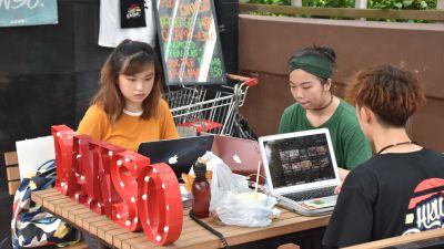 Tre studerande sitter och studerar med sina datorer vid ett bord.