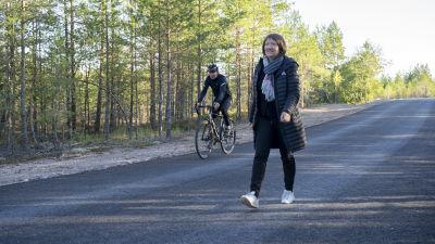 En person går och en annan cyklar på cykelvägen.