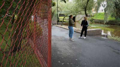 Två kvinnor står på en gångväg och pratar.