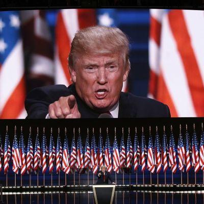 Trump puhujapöntössä, taustalla iso valkokangas, jolla hän näkyysuurennettuna, sekä rivi Yhdysvaltain lippuja.