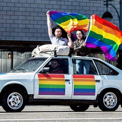 Ohiajavassa autossa ihmiset heilittavat sateenkaarilippuja