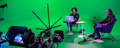 Kamera kuvaa kahta ihmistä green screenin edessä.