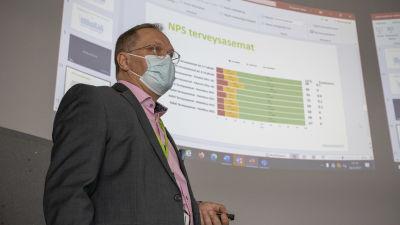 Ilkka Pirskanen håller en presentation. Power point med staplar i bakgrunden.