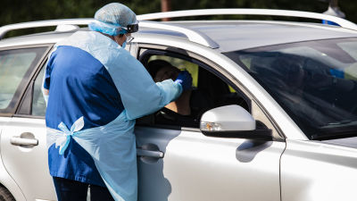 En person i skyddsutrustning tar ett coronatest på en person i en bil.