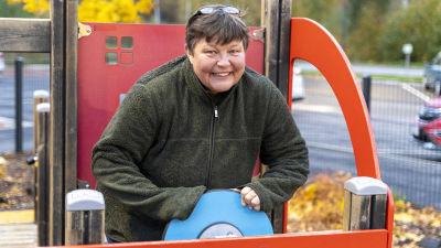 En kvinna i en klätterställning som föreställer en röd bil. Hon finns ute vid daghemmet Karusellen i Karis.